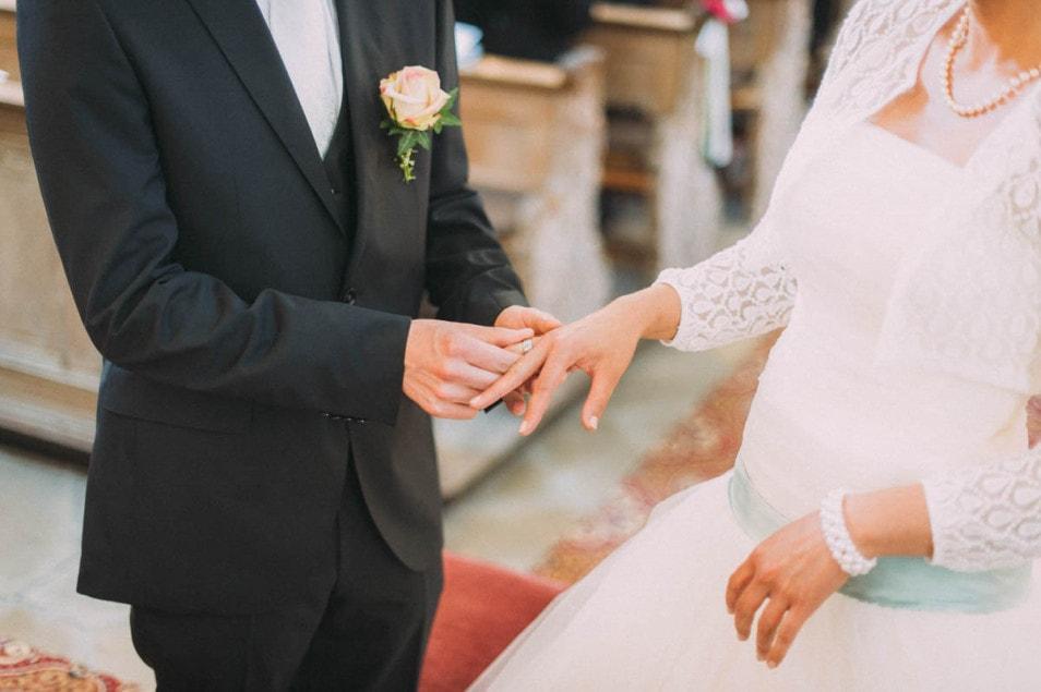 Bräutigam steckt Ring an Finger der Braut