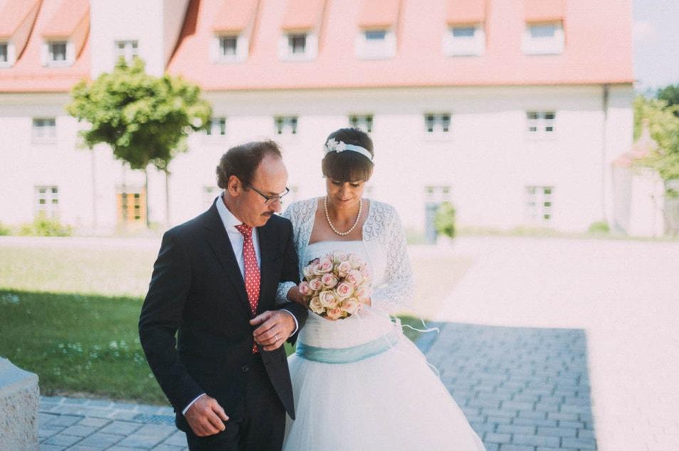 Brautvater bringt die Braut in ihrem Prinzessinnenkleid zur Kirche