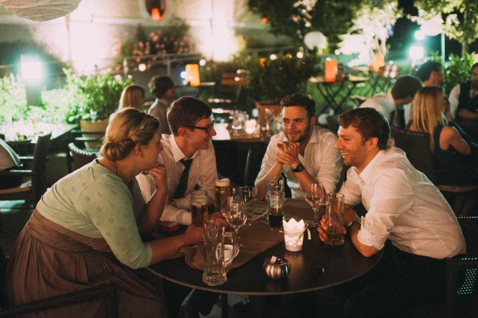 Freunde sitzen beisammen auf der Hochzeit