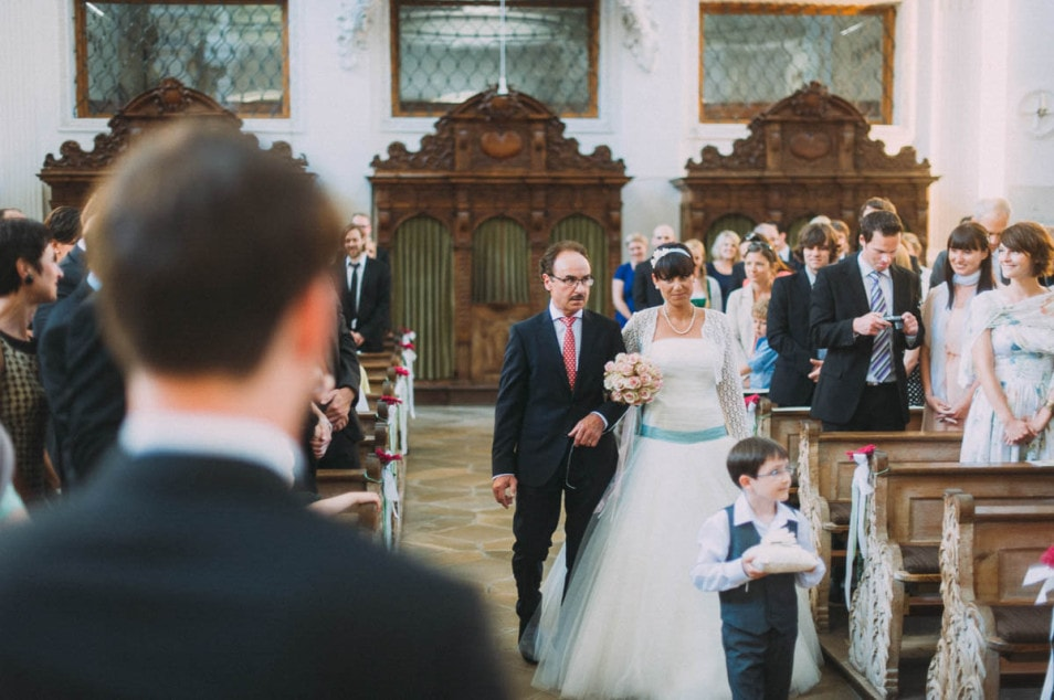 Brautvater bringt Braut in Tüllkleid zum Altar