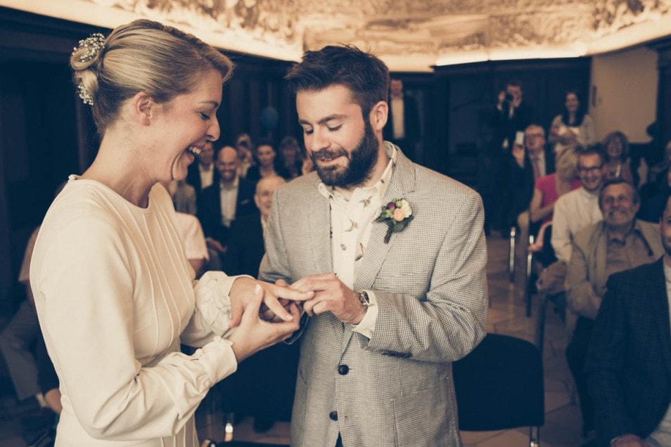 Bräutigam steckt Ring an die Hand der Braut