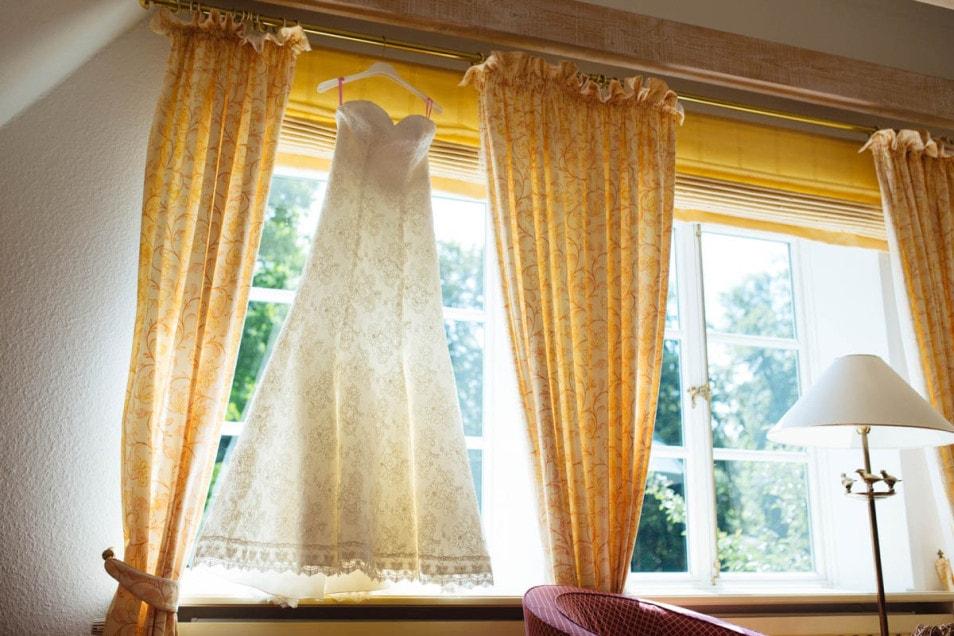 Hochzeit im kleinen Kreis das Hochzeitskleid aus Spitze hängt im Fenster
