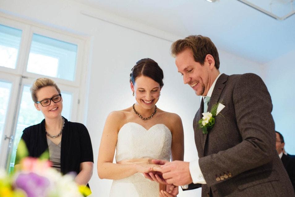 Trauring wird an die rechte Hand der Braut gesteckt