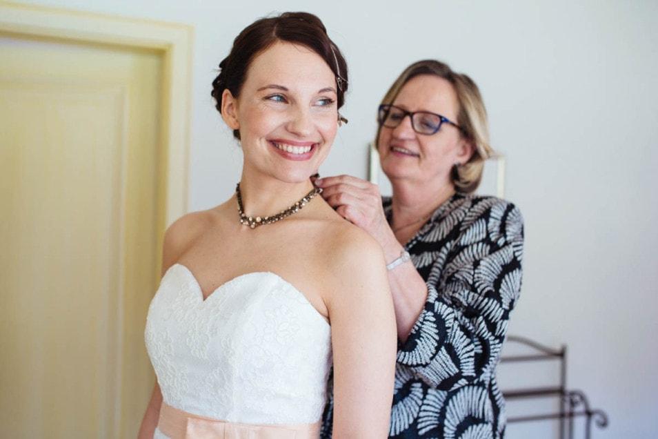 Brautmutter hilft Braut mit dem Brautschmuck