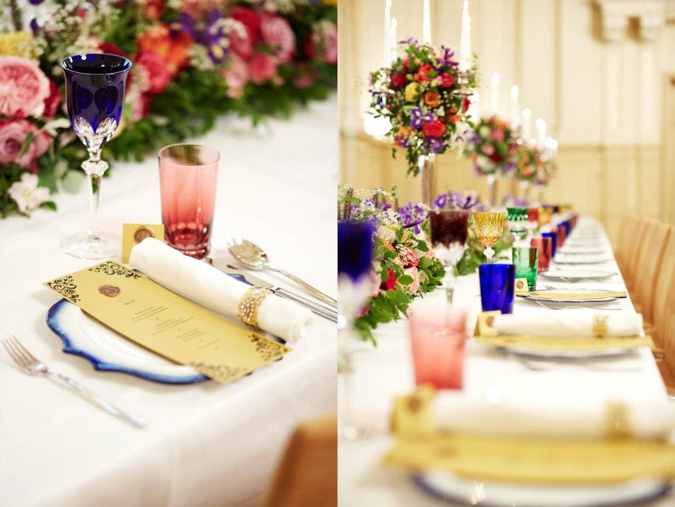 Tischblumen in bunten Farben und Papeterie in Gold