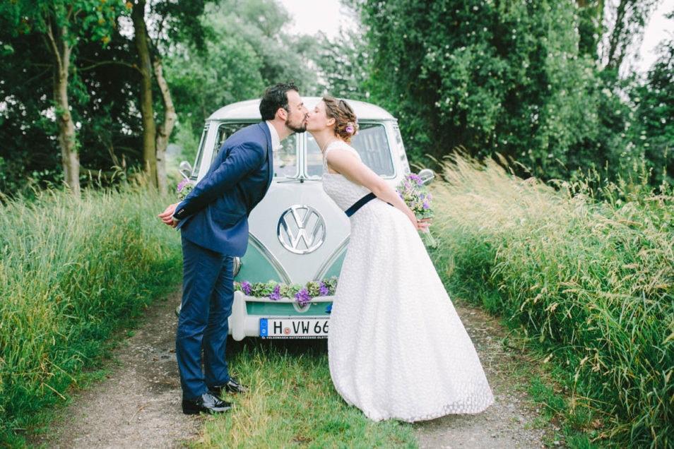 Brautpaar küsst sich vor Hochzeitsbulli