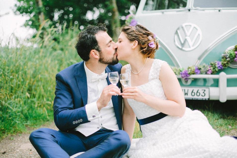 Brautpaar küsst sich vor türkis-farbenen Hochzeitsbulli
