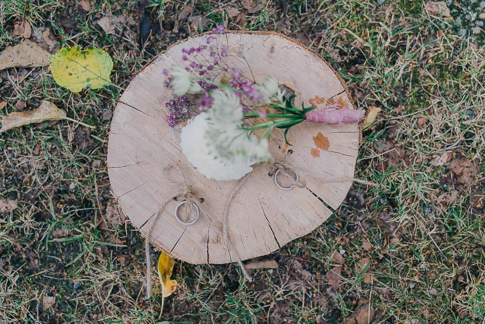 Eheringe mit Blumen auf Holzblock