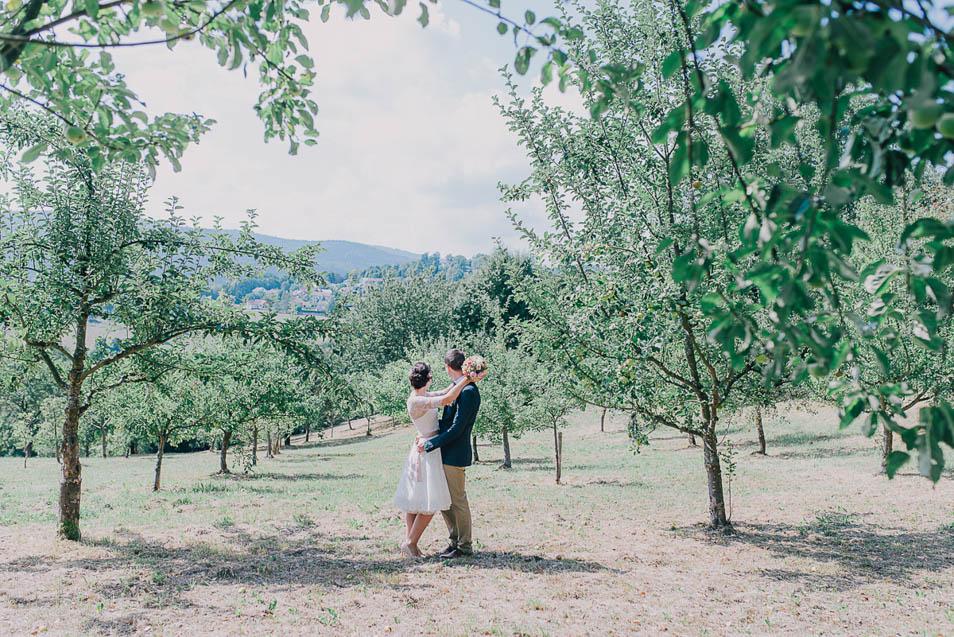 Brautpaar steht auf der Apfelwiese