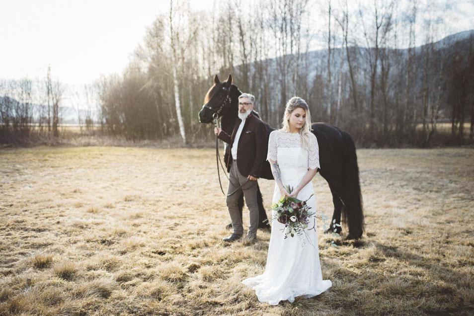 Boho Braut im Hintergrund Bräutigam mit Pferd