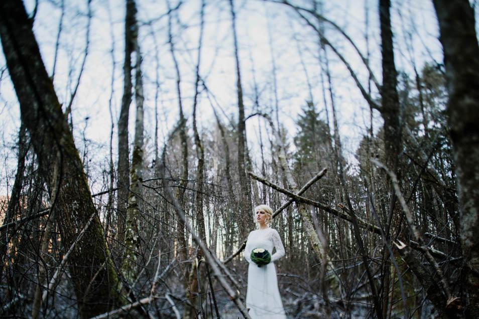 Braut in traumhaftem Brautkleid steht alleine im romantischen Wald