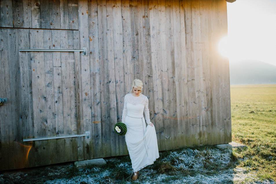 Braut steht in traumhaften Hochzeitskleid vor Hütte in Wintersonne