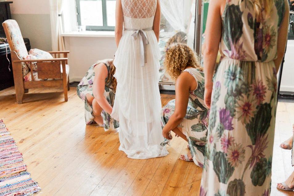 Braut wird von Brautjungfern angezogen