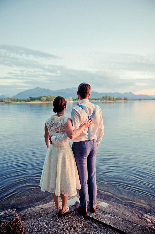 Hochzeitsparty am See, Brautpaar Portraitbild als es auf den See blickt