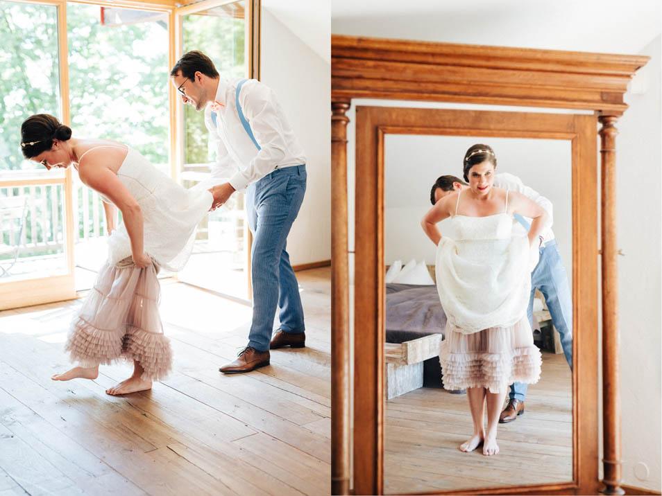 Bräutigam hilft Braut ins Brautkleid