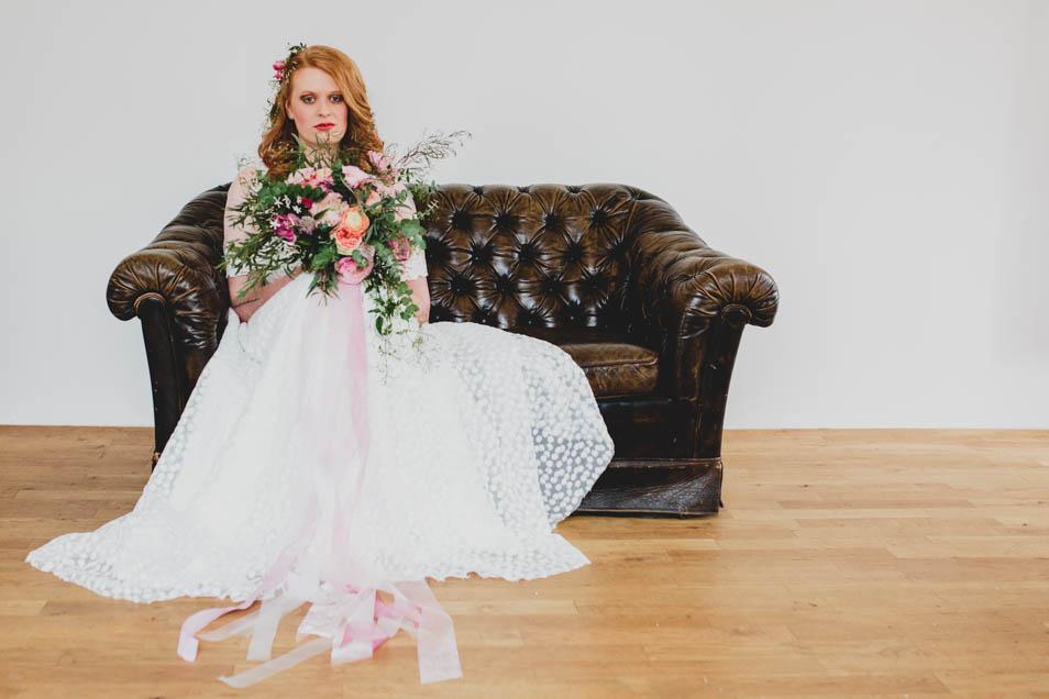 Braut auf Ledersofa mit wundervollem Brautkleid und Strauß