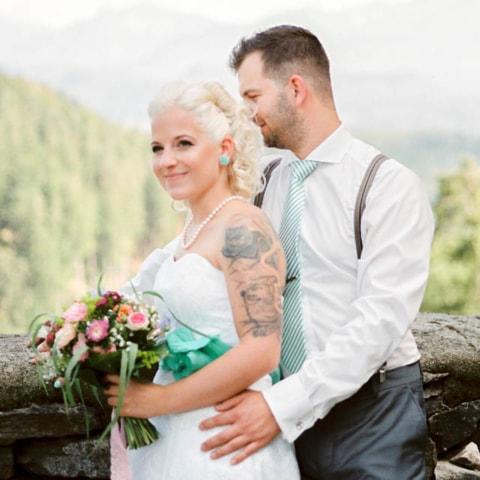 Tätowierte Braut mit Spitzenkleid bei Burghochzeit