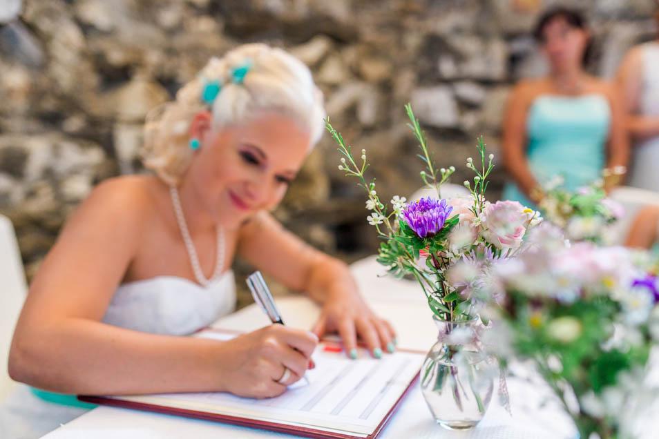 Die Braut unterschreibt nach standesamtlicher Trauung