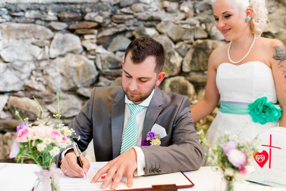 Bräutigam unterschreibt nach standesamtlicher Trauung