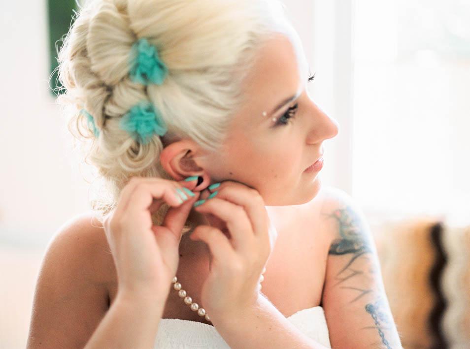 Tätowierte Braut zieht Ohrringe an