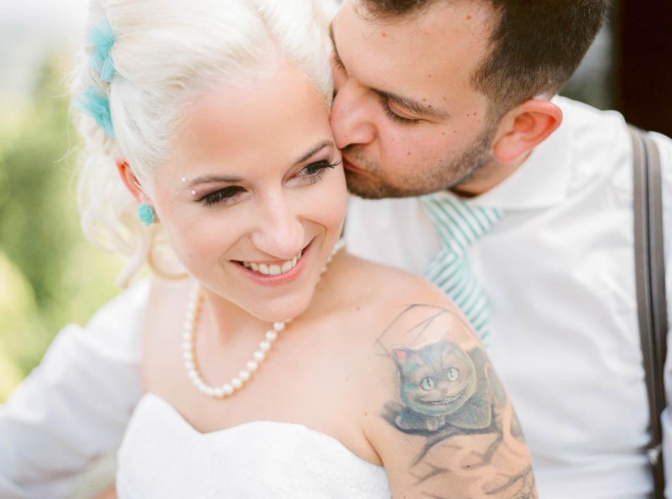 Bräutigam küsst tätowierte Braut auf Wange