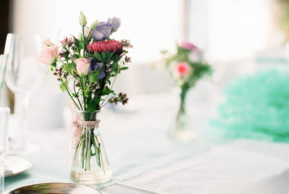 Sommerblumen in kleinen Vasen als Tischschmucke bei Hochzeit