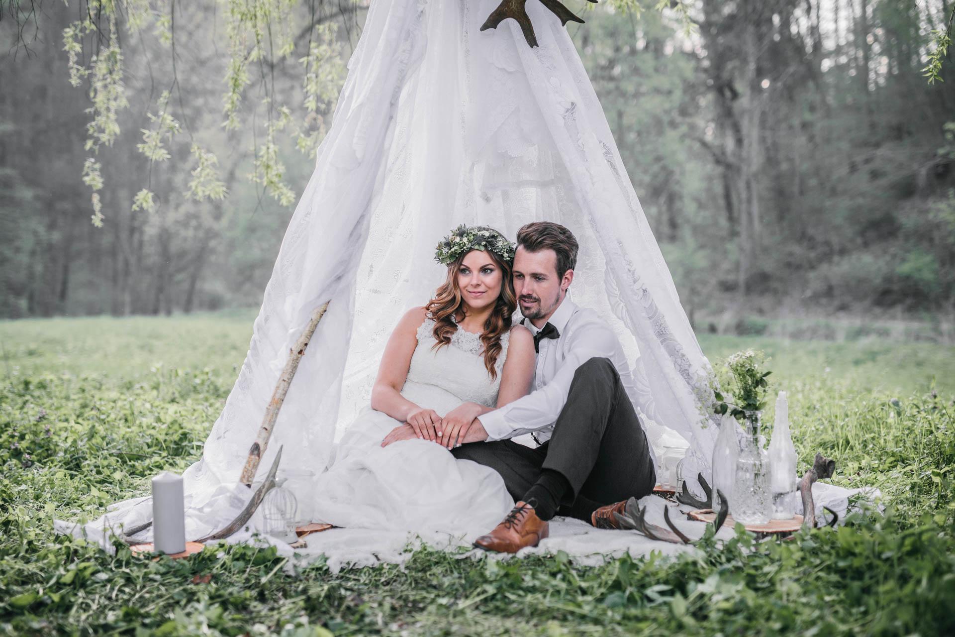 Boho Brautpaar sitzt im Tipi