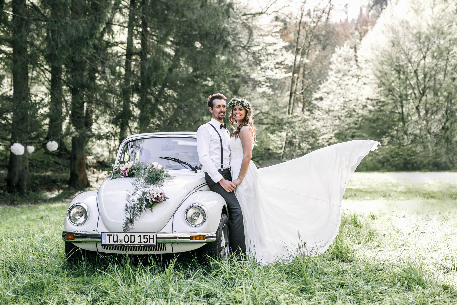 Brautpaar lehnt am Hochzeitsauto (VW Käfer)