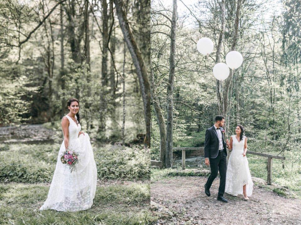 Brautpaar läuft mit Luftballons über Brücke im Wald
