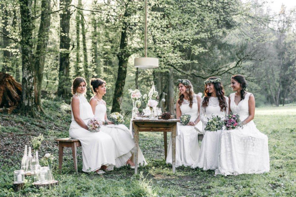 Fünf Bräute mit Boho Brautkleidern am Tisch