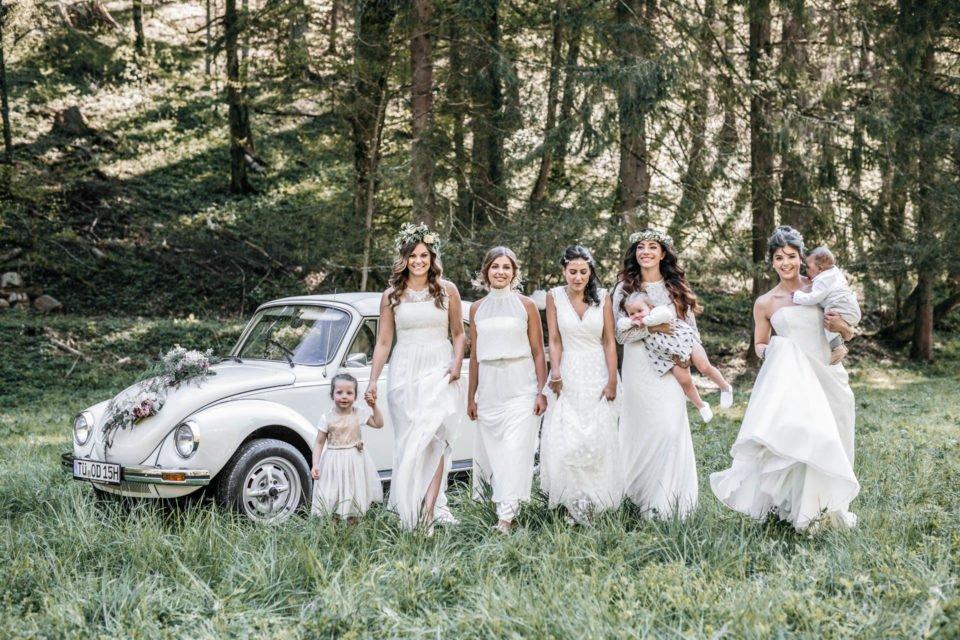 Fünf Boho Bräute mit Blumenkindern im Wald