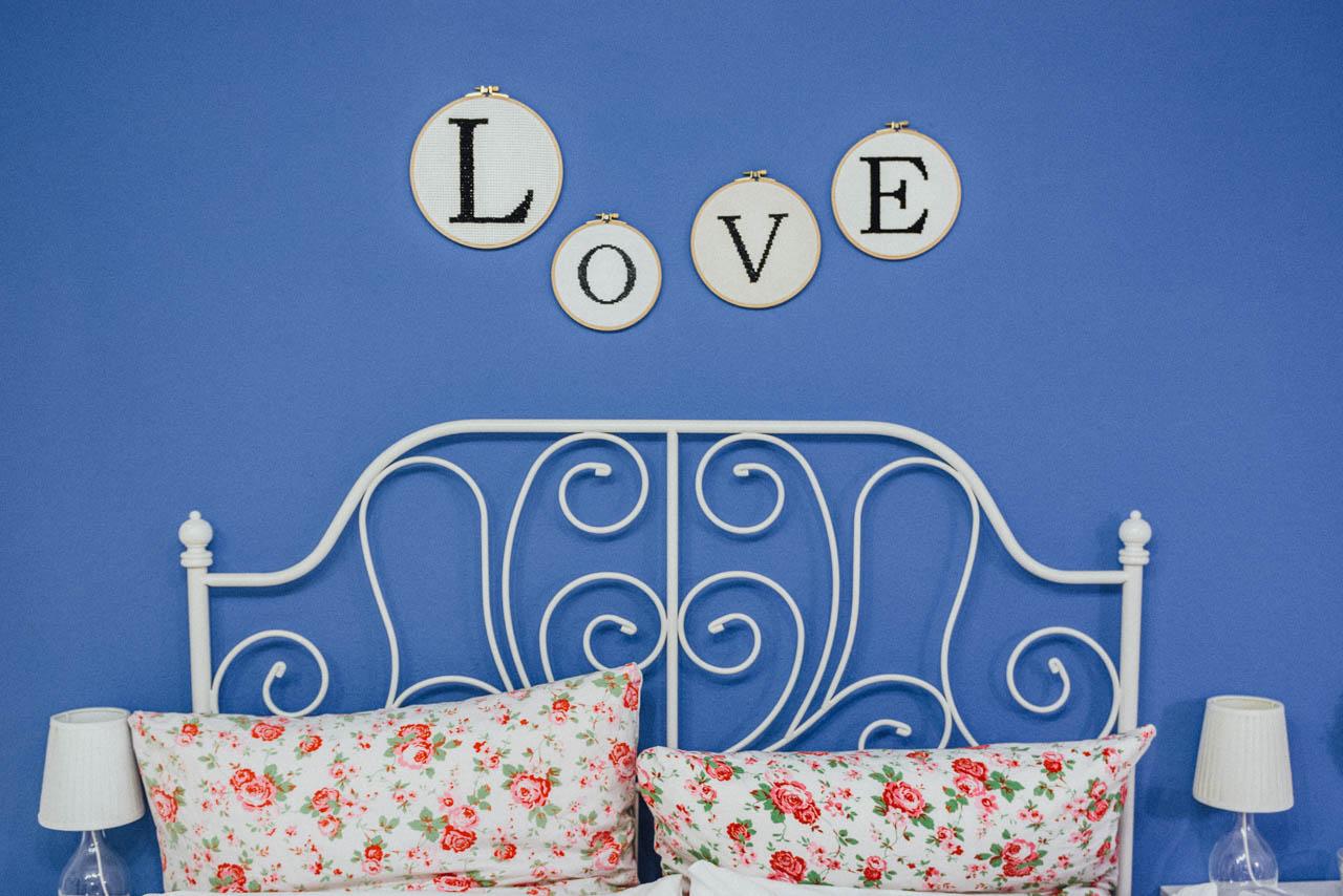 LOVE Schriftzug über dem Bett des Brautpaares