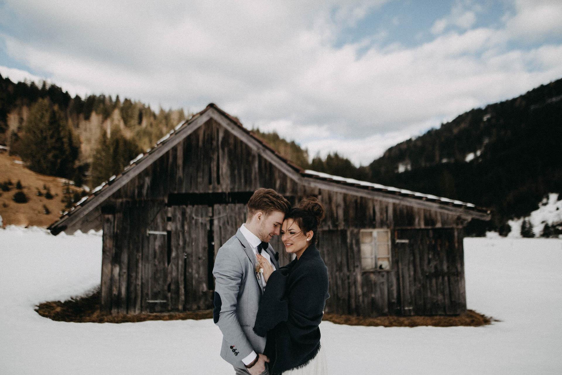 Brautpaar im Schnee mit Spitzen Brautkleid
