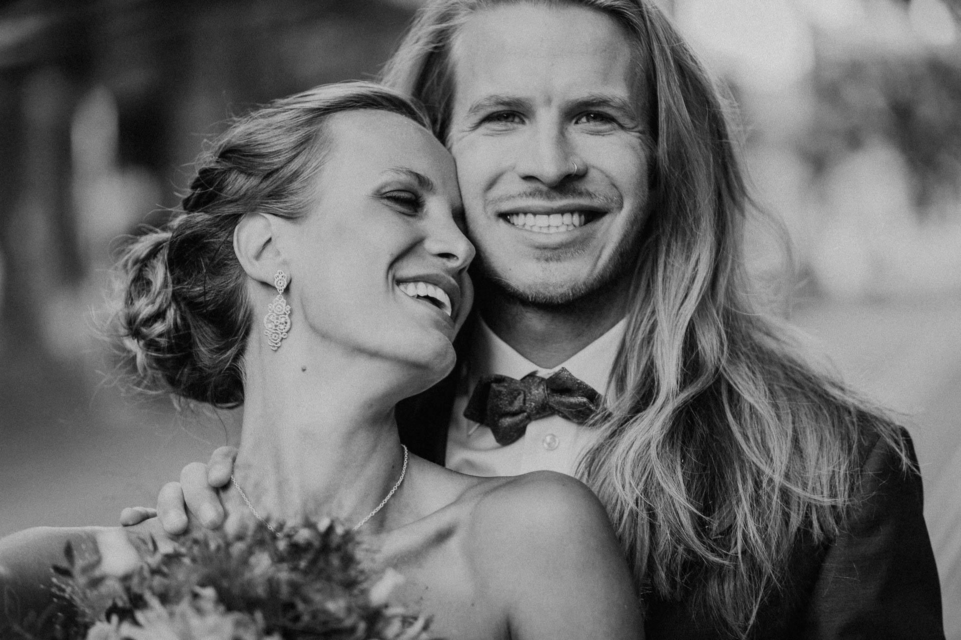 Braut lehnt sich an Bräutigam, beide strahlen
