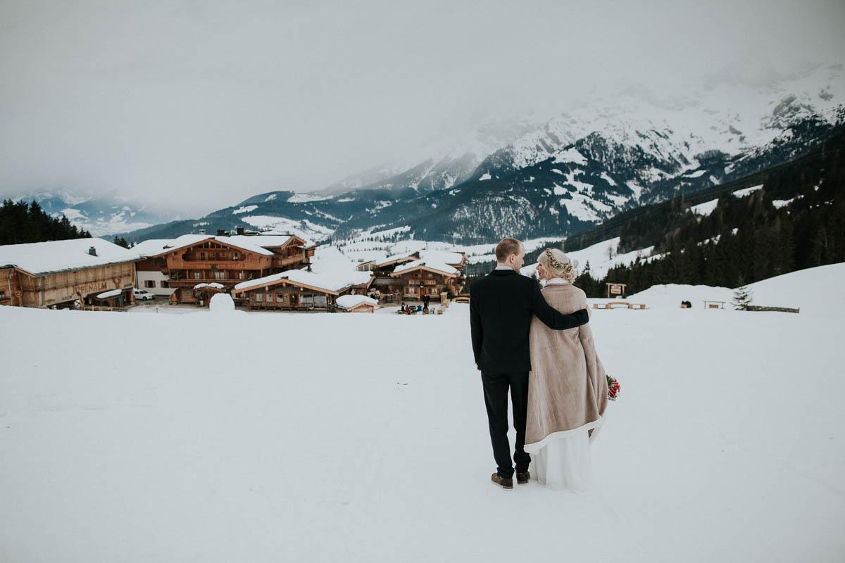 Brautpaar blickt ins verschneite Tal