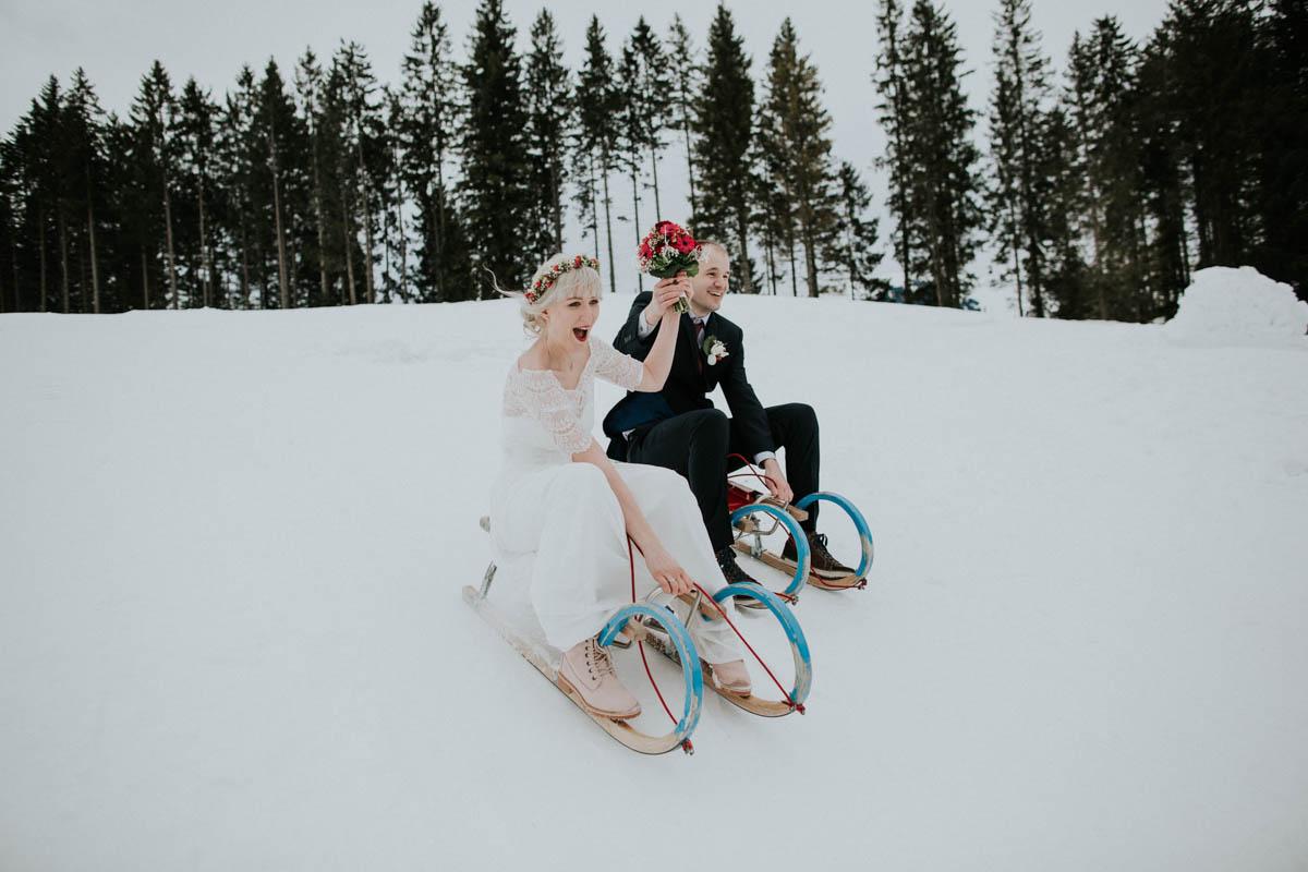 Brautpaar fährt Schlitten bei der Hochzeit im Schnee