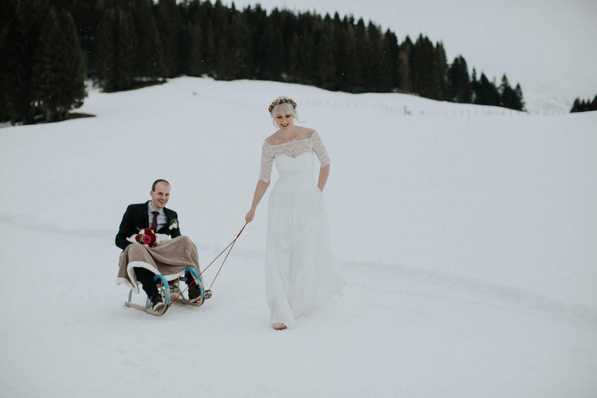 Braut zieht Bräutigam auf dem Schlitten