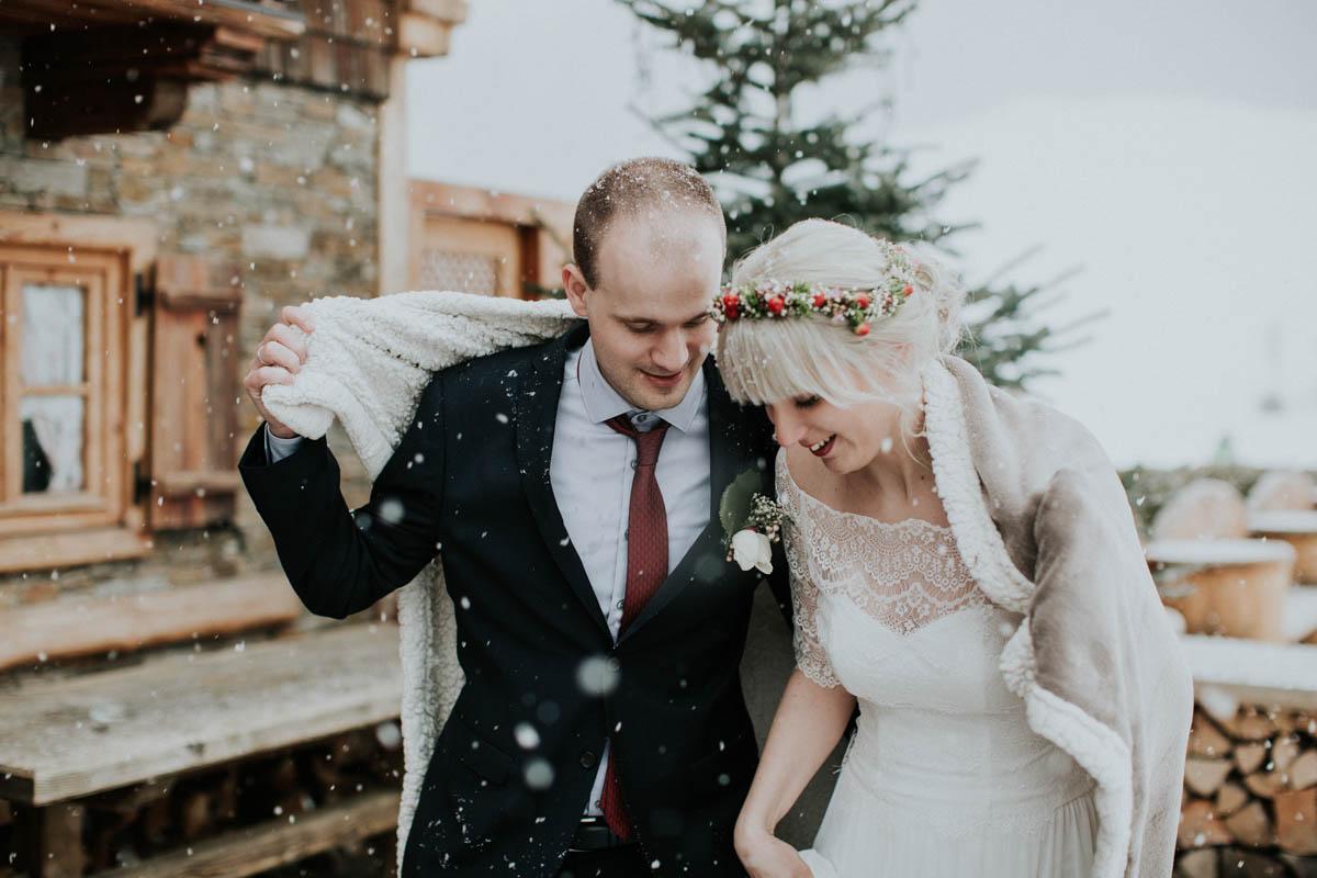 Brautpaar zieht Decke über die Schultern während es schneit
