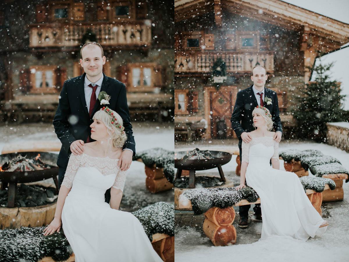 Bräutigam steht hinter Braut und die Schneeflocken rieseln auf sie herab