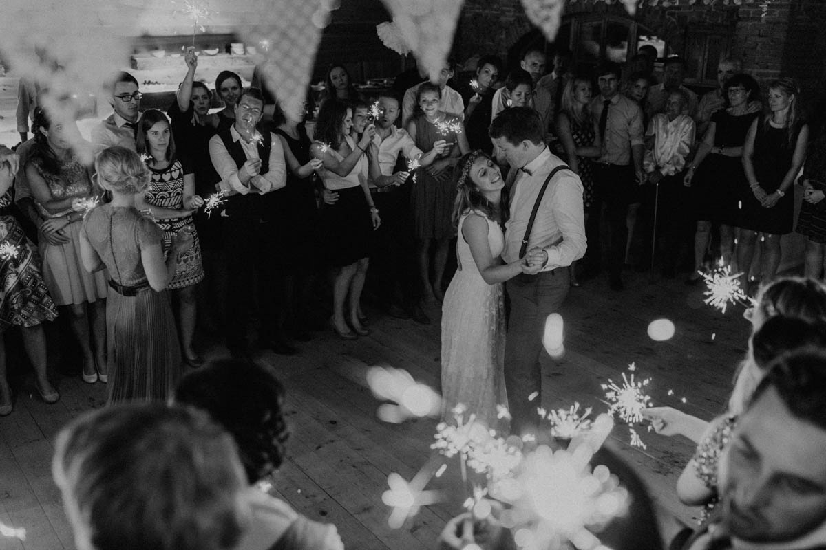 Brautpaar tanzt während Hochzeitsgesellschaft Wunderkerzen hält