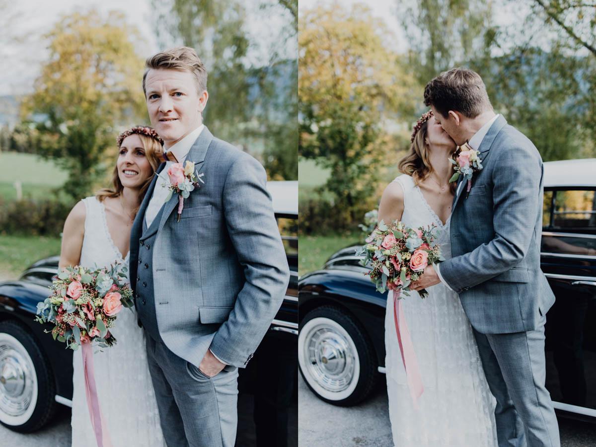 Brautpaar küsst sich vor Hochzeitsauto