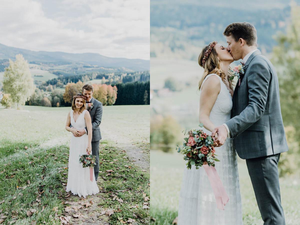 Brautpaar küsst sich auf der Wiese