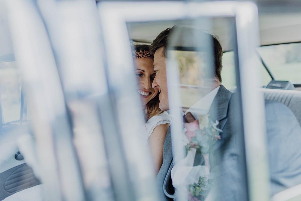 Brautpaar lächelt sich im Hochzeitsauto an
