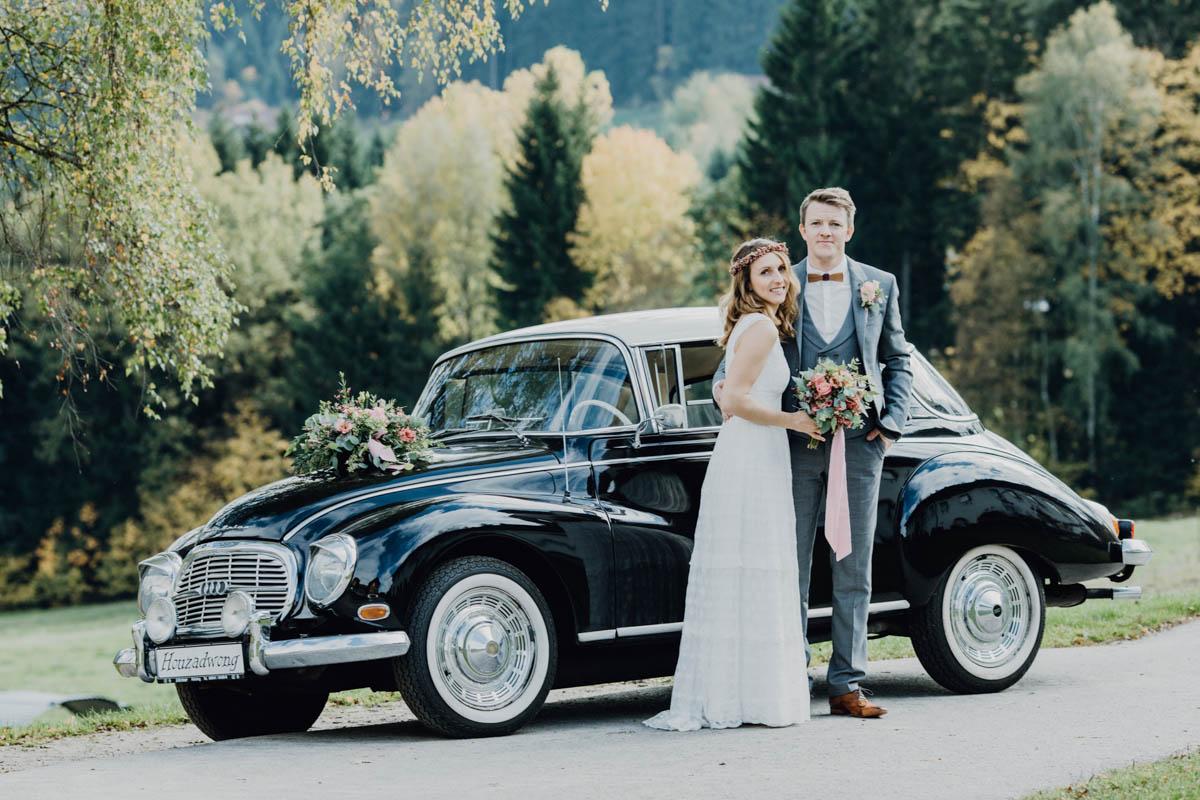 Brautpaar vor Hochzeitsauto