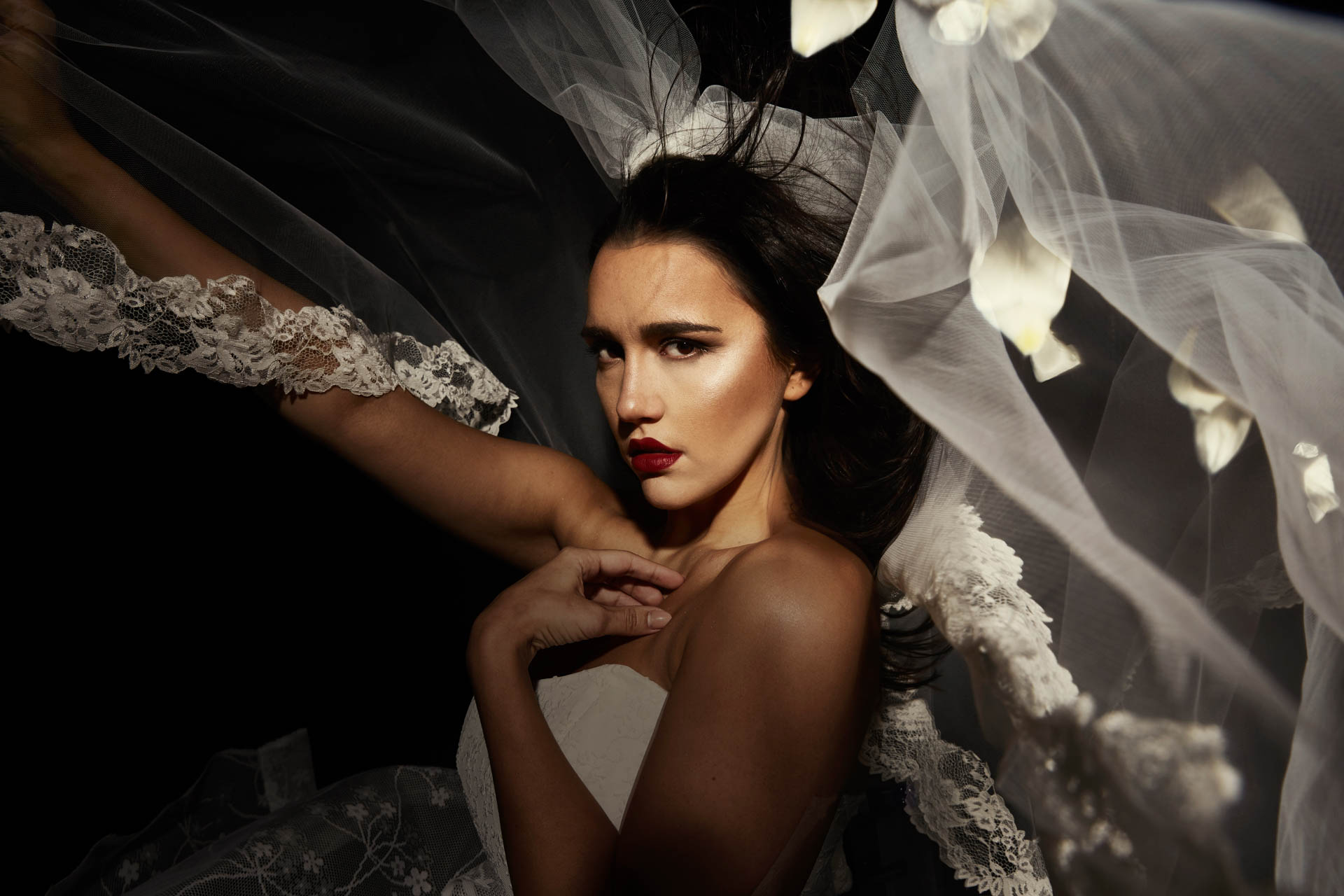 Plus Size Model im Brautkleid mit fliegendem Schleier