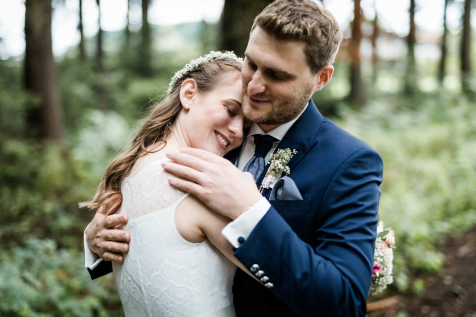 Brautpaar umarmt sich im Wald