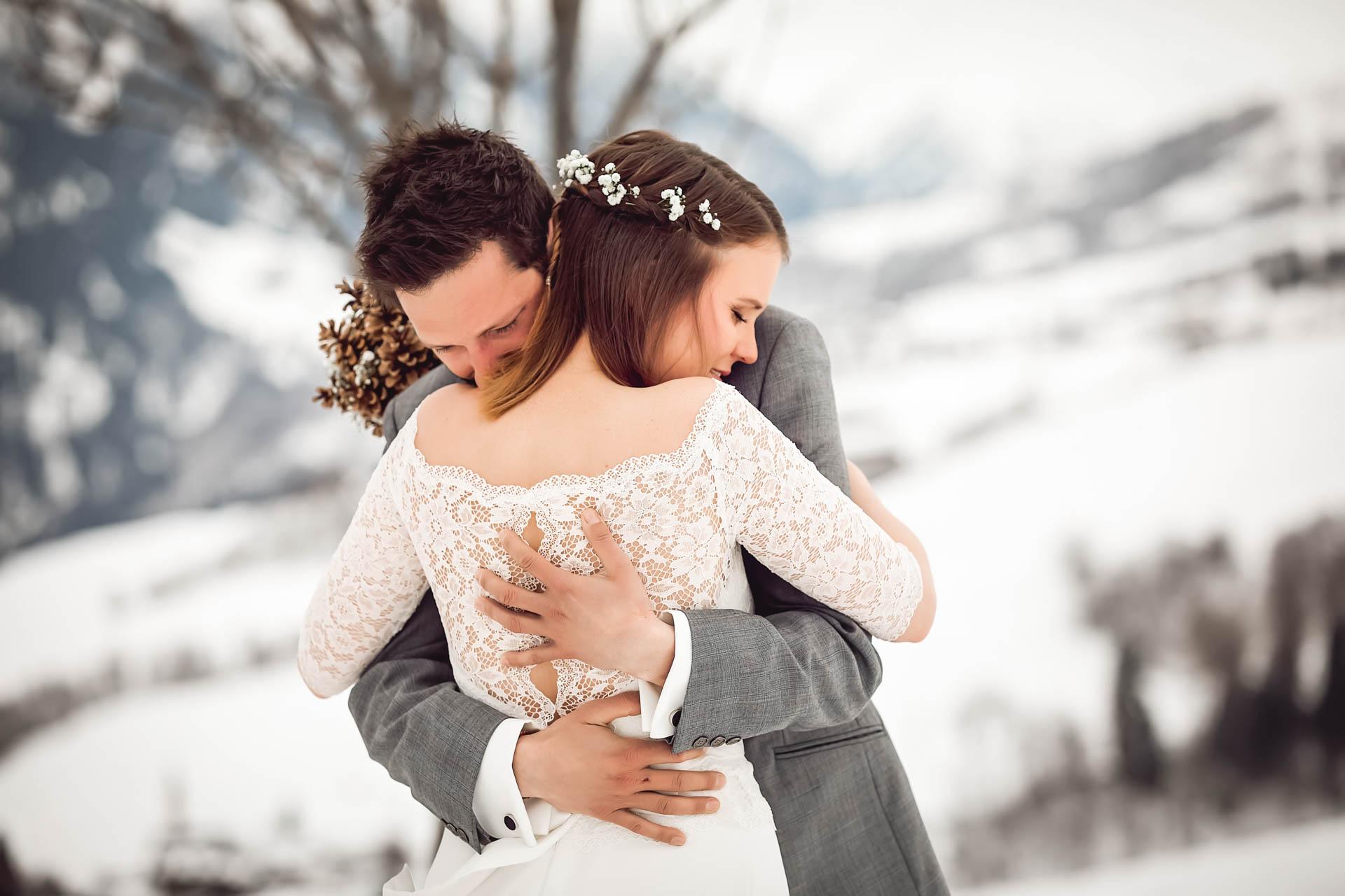 Brautpaar umarmt sich bei Winterhochzeit in den Bergen