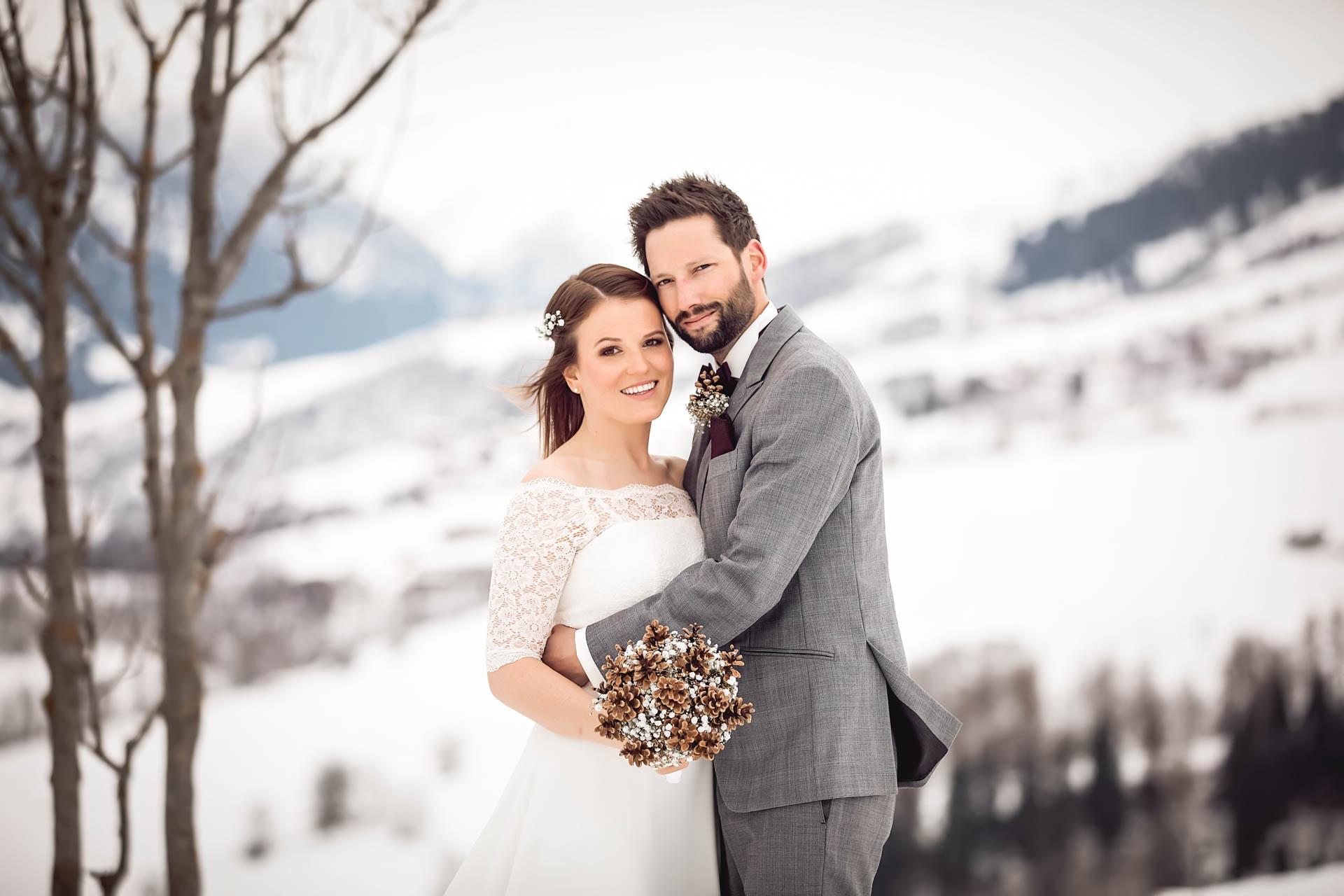 Winterhochzeit in den Bergen - glückliches Brautpaar