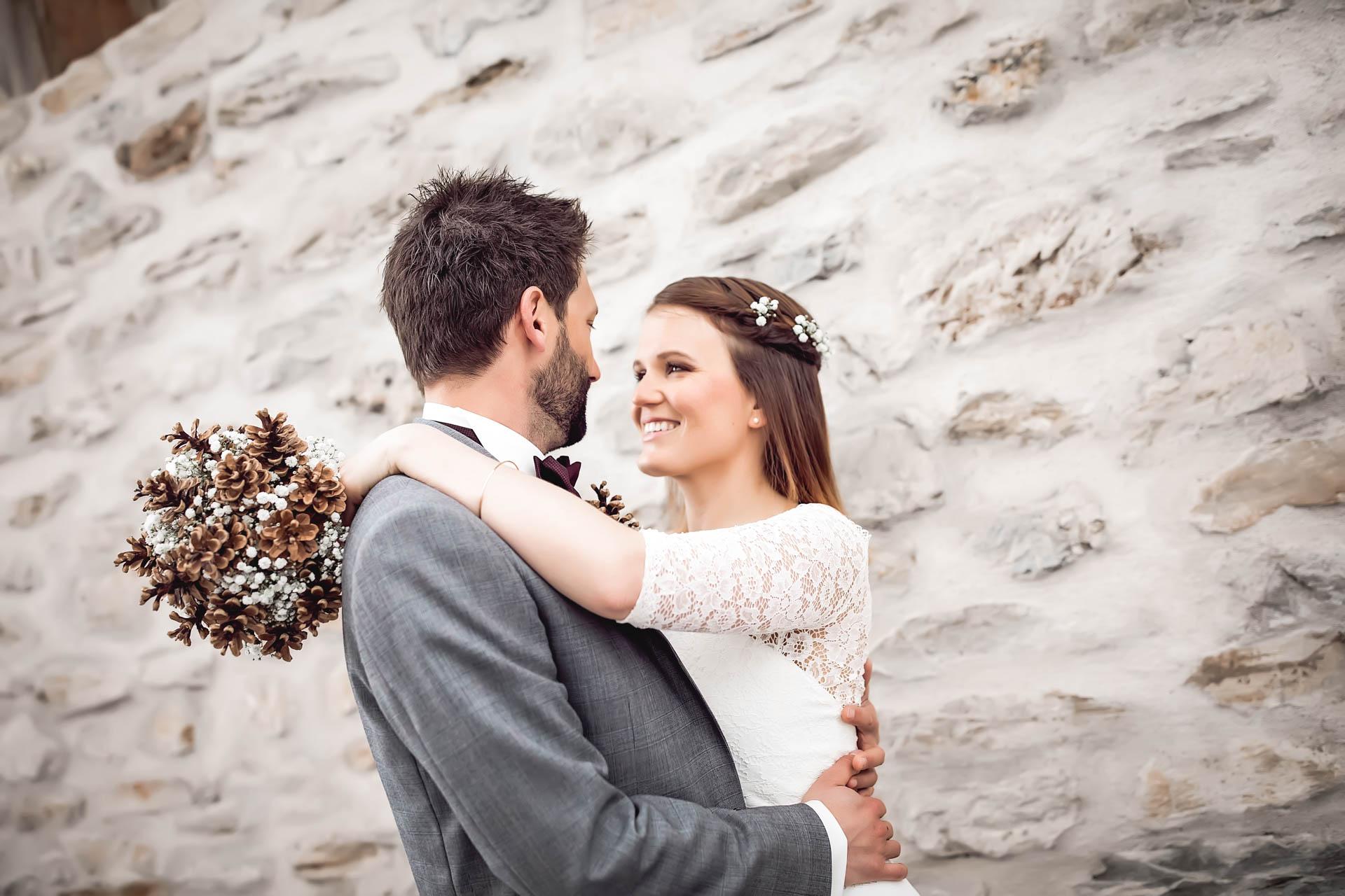 Braut mit winterlichem Brautstrauss himmelt ihren Bräutigam an