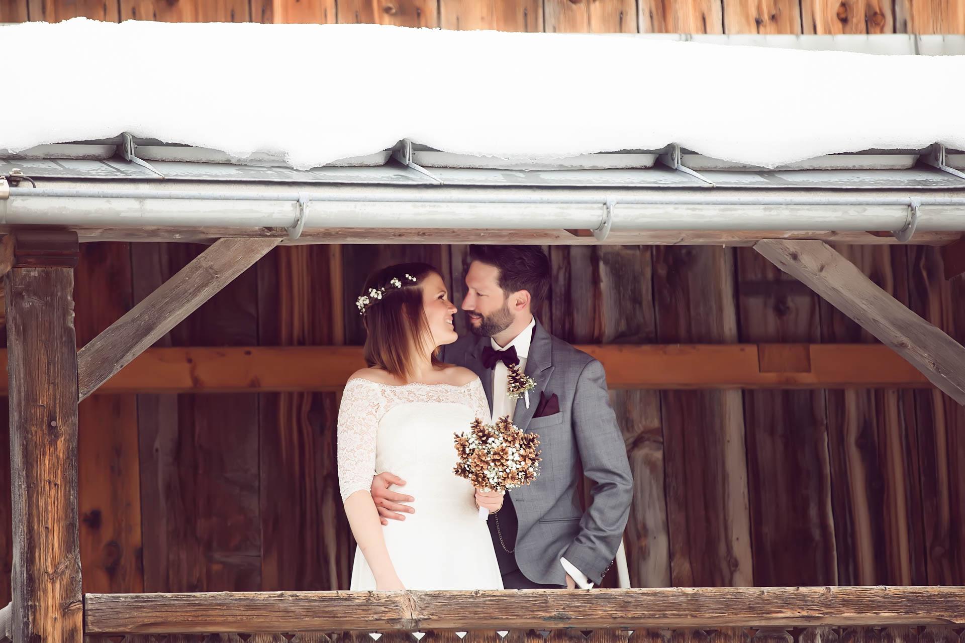 Brautpaar umarmt sich unter Schnee bedecktem Dach